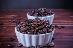Chicchi di caffè arrostiti in porcellana bianca della ciotola su backg di legno Fotografia Stock