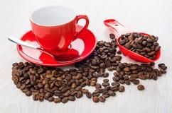 Chicchi di caffè arrostiti sparsi, fagioli in cucchiaio di plastica, Cu vuoto Fotografia Stock