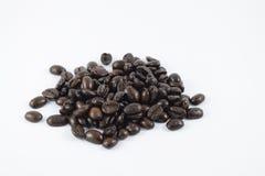 Chicchi di caffè arrostiti su priorità bassa bianca Immagine Stock