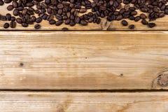 Chicchi di caffè arrostiti su una tavola di legno Immagine Stock