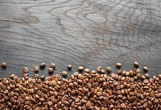 Chicchi di caffè arrostiti sulla tabella di legno Vista superiore immagine stock