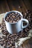 Chicchi di caffè arrostiti in una tazza della porcellana Fotografie Stock