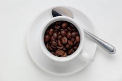 Chicchi di caffè arrostiti in una tazza di caffè contro fondo bianco con spazio per testo, vista da sopra Fotografie Stock Libere da Diritti