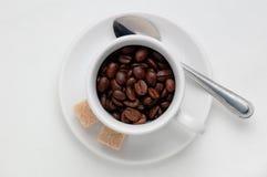 Chicchi di caffè arrostiti in una tazza di caffè contro fondo bianco, vista superiore con spazio per testo Fotografia Stock