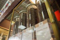 Chicchi di caffè in boccette Tazze di caffè e chicchi di caffè freschi intorno Vendita dei chicchi di caffè Vendita Immagini Stock