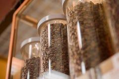 Chicchi di caffè in boccette Tazze di caffè e chicchi di caffè freschi intorno Vendita dei chicchi di caffè Vendita Fotografia Stock