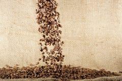 Chicchi di caffè che cadono giù sul fondo del sacco Fotografia Stock