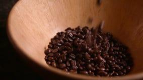 Chicchi di caffè che cadono nella ciotola di legno al rallentatore archivi video