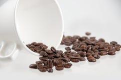 chicchi di caffè che si rovesciano da una tazza Fotografie Stock Libere da Diritti