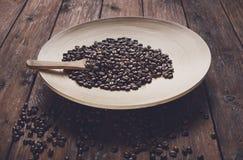 Chicchi di caffè in ciotola con il cucchiaio di legno sulla tavola Immagine Stock