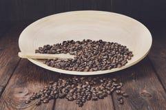 Chicchi di caffè in ciotola con il cucchiaio di legno sulla tavola Fotografie Stock