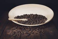Chicchi di caffè in ciotola con il cucchiaio di legno sulla tavola Immagini Stock Libere da Diritti