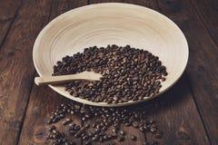 Chicchi di caffè in ciotola con il cucchiaio di legno sulla tavola Fotografia Stock