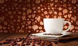 Chicchi di caffè con caffè sulla tavola Immagini Stock