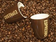 Chicchi di caffè con due tazze del caffè espresso Immagini Stock