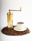 Chicchi di caffè con la smerigliatrice e la tazza di coffe Immagine Stock