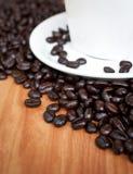 Chicchi di caffè con la tazza di caffè macchiato. Fotografia Stock