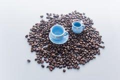 Chicchi di caffè con le stoviglie blu del caffè espresso Immagini Stock