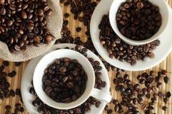 Chicchi di caffè con una tazza e un sacco bianchi Fotografia Stock