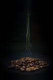 Chicchi di caffè con vapore in aumento su fondo nero immagine stock libera da diritti