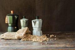 Chicchi di caffè crudi con il vaso di moka in un sacco sulla tavola Fotografia Stock Libera da Diritti