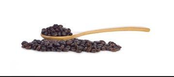 Chicchi di caffè in cucchiaio di legno su fondo bianco Fotografia Stock