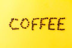 Chicchi di caffè delle lettere su fondo vibrante giallo Minimalismo FO Fotografia Stock