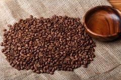 Chicchi di caffè di Brown sulla borsa con il piatto di legno vuoto Fotografia Stock