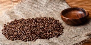 Chicchi di caffè di Brown sulla borsa con il piatto di legno vuoto Immagine Stock Libera da Diritti
