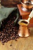 Chicchi di caffè di natura morta in un vaso del rame e della borsa Fotografie Stock Libere da Diritti