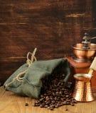 Chicchi di caffè di natura morta in un vaso del rame e della borsa Immagine Stock
