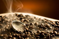 Chicchi di caffè di torrefazione con fumo fotografia stock libera da diritti