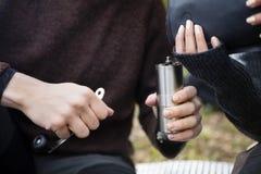 Chicchi di caffè di versamento della donna nella smerigliatrice Held By Man immagine stock