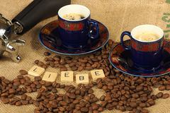 Chicchi di caffè, due tazze decorate e maniglia del gruppo con le lettere Liebe su un fondo della tela di iuta Fotografia Stock