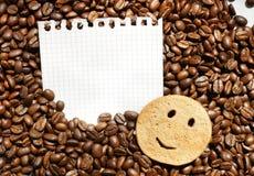 Chicchi di caffè e biscotto sorridente sullo strato del taccuino Fotografia Stock
