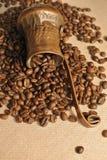 Chicchi di caffè e caffettiera turca di rame d'annata (cezve o ibrik) sul sacco del panno Fotografie Stock