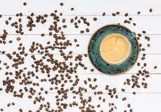Chicchi di caffè e della tazza di caffè sulla tavola di legno bianca Vista superiore Fotografia Stock