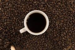 Chicchi di caffè e della tazza di caffè su vecchio fondo di legno Fotografia Stock Libera da Diritti