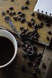 Chicchi di caffè e della tazza di caffè sulla tavola di legno immagini stock libere da diritti