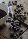 Chicchi di caffè e della tazza di caffè sulla tavola di legno fotografia stock
