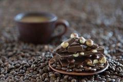 Chicchi di caffè e fine nera del cioccolato su fotografie stock libere da diritti