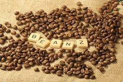 Chicchi di caffè e le lettere BEANZ su un fondo della tela di iuta Immagini Stock