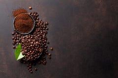 Chicchi di caffè e polvere a terra immagini stock