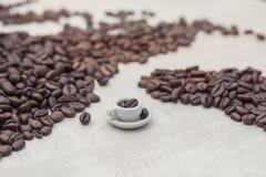 Chicchi di caffè e tazza del giocattolo con caffè, concetto Fotografia Stock Libera da Diritti