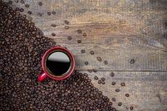 Chicchi di caffè e tazza di caffè rossa Fotografia Stock