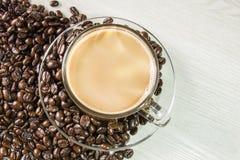 Chicchi di caffè e tazza di caffè su fondo di legno bianco Immagine Stock