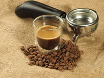 Chicchi di caffè e tazza di vetro davanti ad una maniglia del gruppo su un fondo della tela di iuta Fotografia Stock