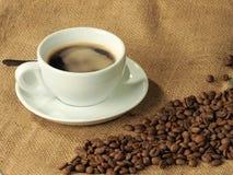 Chicchi di caffè e una tazza bianca di caffè nero su un fondo della tela di iuta Immagini Stock
