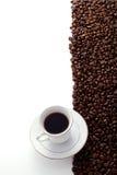 Chicchi di caffè e una tazza e un piattino fotografia stock