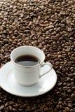 Chicchi di caffè e una tazza e un piattino immagine stock